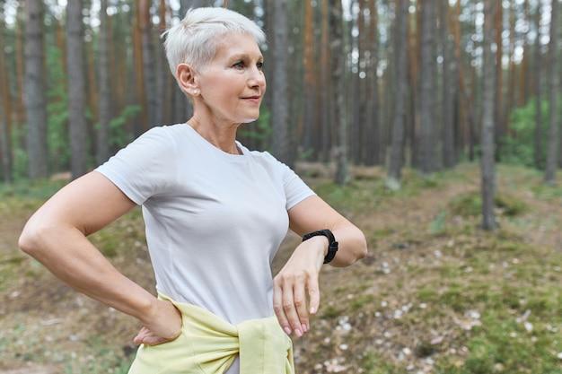 Mensen, sport, gezondheid en techniek. actieve gepensioneerde vrouw die slim horloge draagt om haar voortgang tijdens cardio-oefeningen buitenshuis te volgen. Gratis Foto