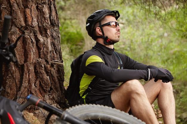 Mensen, sport, natuur en vrije tijd concept. ontspannen zorgeloze blanke fietser in wielerkleding en beschermende uitrusting met een kleine pauze tijdens de ochtendtraining, met zijn e-bike bij hem in de buurt Gratis Foto