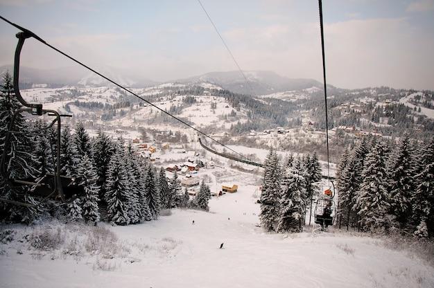 Mensen stijgen op met de lift in de karpaten. detailopname. winter natuur. er valt zware sneeuw. bovenaanzicht. en naar beneden kijken. Premium Foto