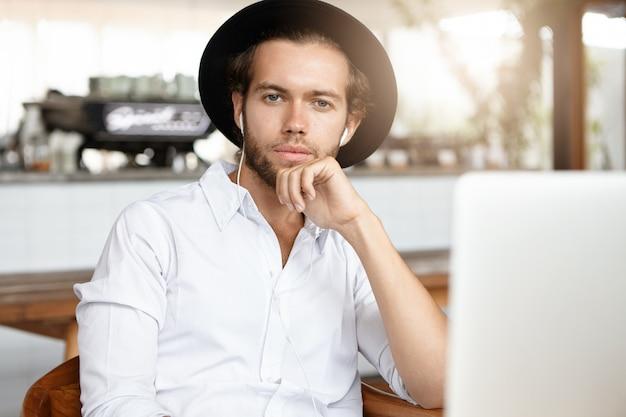 Mensen, technologie en vrije tijd concept. modieuze jonge man met baard luisteren naar liedjes op oortelefoons, met behulp van online muziek-app op zijn laptopcomputer Gratis Foto