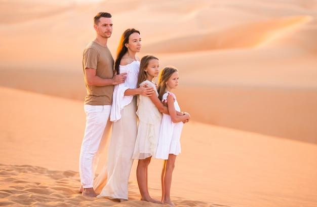 Mensen tussen de duinen in de rub al-khali-woestijn in de verenigde arabische emiraten Premium Foto