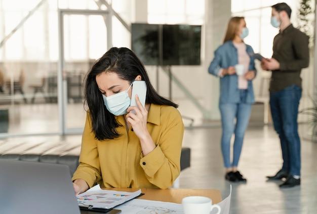 Mensen uit het bedrijfsleven dragen medische maskers op het werk Gratis Foto