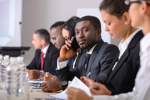 Mensen uit het bedrijfsleven in formalwear bespreken iets. Premium Foto