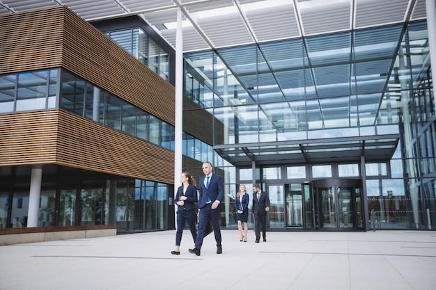 Mensen uit het bedrijfsleven lopen buiten kantoorgebouw Gratis Foto