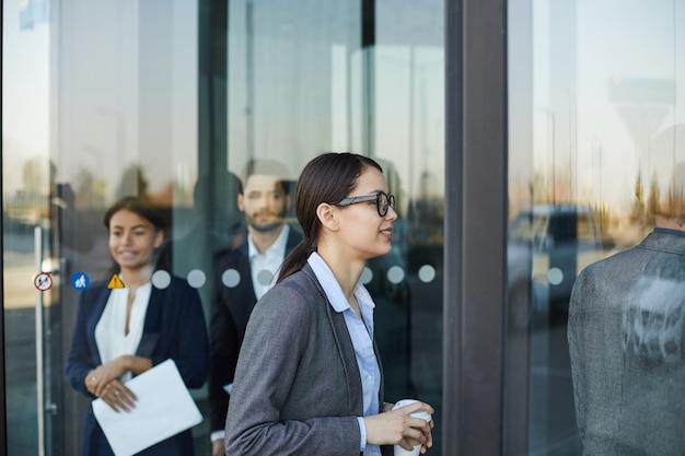 Mensen uit het bedrijfsleven lopen door draaideur Premium Foto