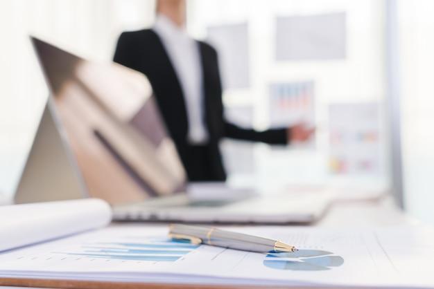 Mensen uit het bedrijfsleven met behulp van laptop en financiële grafieken op de vergadering van o Gratis Foto
