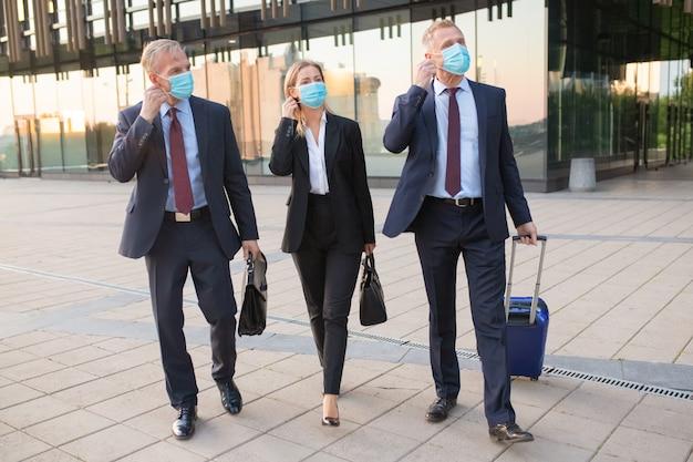 Mensen uit het bedrijfsleven passen zich aan of zijn klaar om gezichtsmaskers af te doen tijdens het wandelen met bagage buitenshuis, in de buurt van kantoorgebouwen. zakenreis en einde van epidemisch concept Gratis Foto