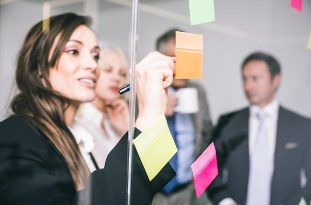 Mensen uit het bedrijfsleven praten en notities schrijven op de post-it Premium Foto