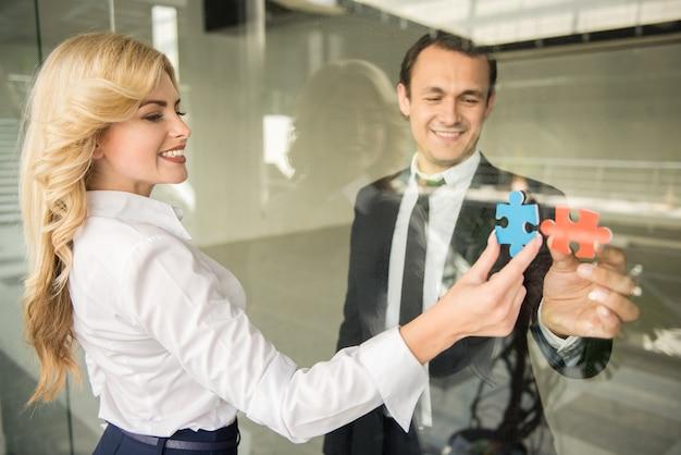 Mensen uit het bedrijfsleven proberen kleine stukjes van de puzzel te verbinden. Premium Foto