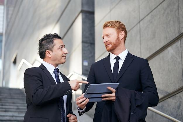 Mensen uit het bedrijfsleven werken buiten kantoorgebouw Premium Foto