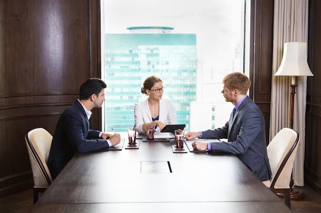 Grote Houten Tafels : Mensen uit het bedrijfsleven zitten aan een grote houten tafel met