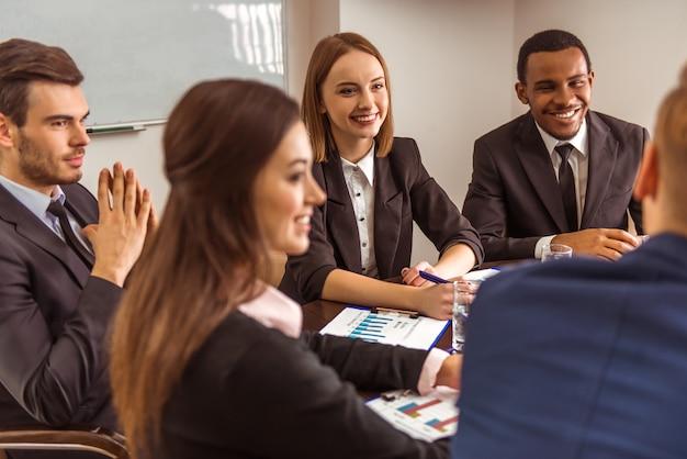 Mensen uit het bedrijfsleven zitten aan een tafel en bespreken iets. Premium Foto