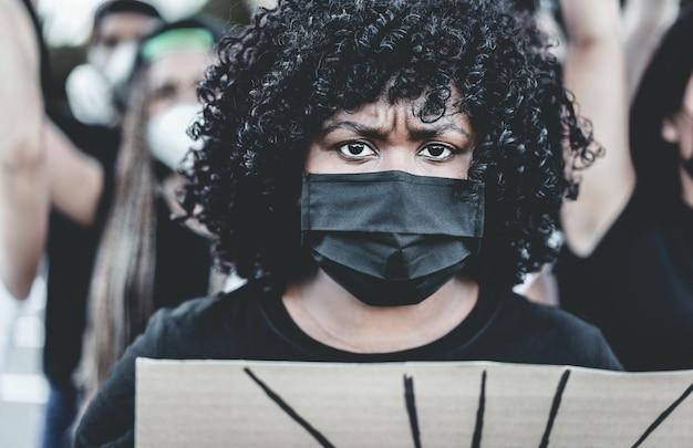 Mensen uit verschillende culturen en rassen protesteren op straat voor gelijke rechten - demonstranten die gezichtsmaskers dragen tijdens een campagne ter bestrijding van het leven van zwarte levens - belangrijkste focus op masker Premium Foto