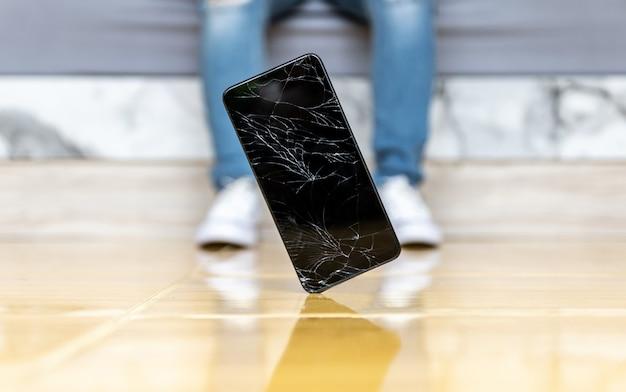 Mensen vallen smartphone op het vloer gebroken scherm Premium Foto