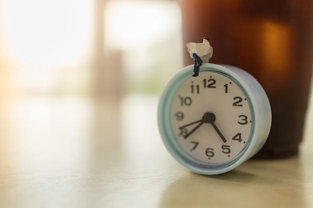 Mensen van het zakenman de miniatuurcijfer die en een krant op uitstekende ronde klok zitten met meeneem plastic kop bevroren zwarte koffie op houten lijst met exemplaarruimte zitten. Premium Foto