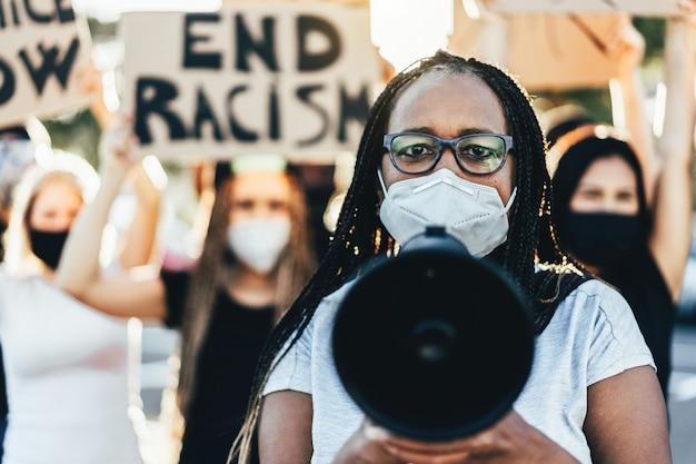 Mensen van verschillende leeftijden en rassen protesteren op straat voor gelijke rechten - demonstranten die gezichtsmaskers dragen tijdens de strijd tegen het zwarte leven zijn belangrijk - focus op het gezicht van de vrouw Premium Foto