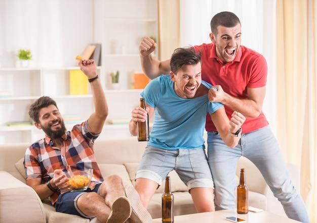 Mensen verheugen zich over een doelpunt gescoord in een appartement. Premium Foto