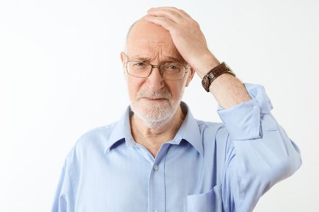 Mensen, veroudering en gezondheidsproblemen concept. gefrustreerde ongelukkige bejaarde blanke man met grijze baard die hand op zijn kale hoofd houdt met vergeetachtige gezichtsuitdrukking, lijdt aan geheugenverlies Gratis Foto