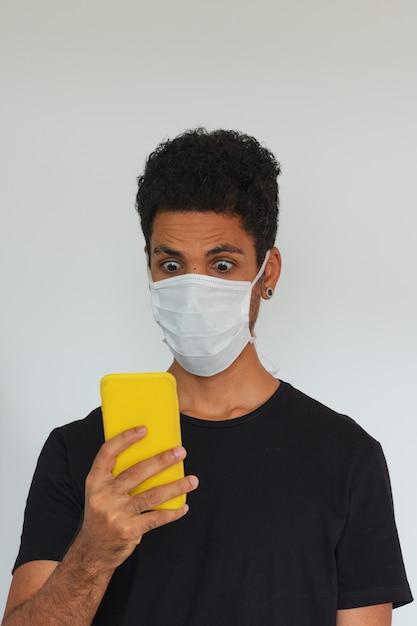 Mensen volwassen zwarte dragende coronavirus de celtelefoon van de maskerholding die op wit wordt geïsoleerd Premium Foto