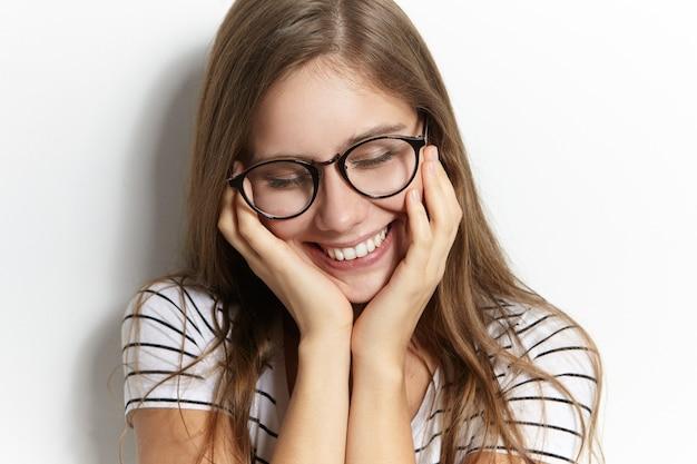 Mensen, vreugde, jeugd en geluk concept. close-up foto van charmante timide tienermeisje in stijlvolle transparante brillen verlegen naar beneden kijken en breed glimlachen, gezicht aanraken, beschaamd Gratis Foto