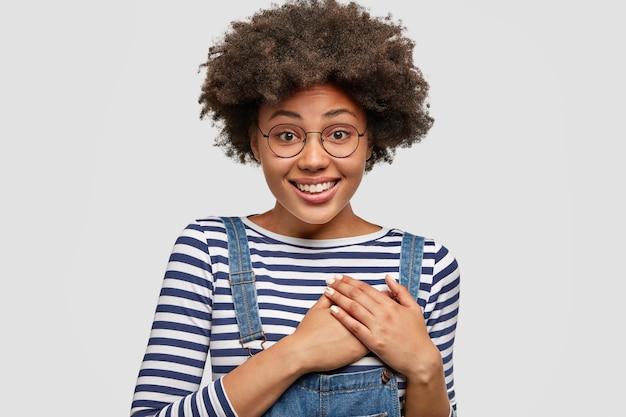 Mensen, vriendelijkheid en gevoelens concept. tevreden aantrekkelijke afro-amerikaanse vrouw houdt de handen op het hart, betuigt medeleven, draagt een gestreepte trui met tuinbroek, geïsoleerd over witte muur Gratis Foto