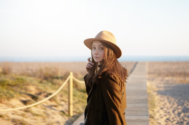 Mensen, vrije tijd, levensstijl en reizen. gelukkig en zorgeloos brunette vrouw wandelen langs de kust, haar losse haren aanraken en zich omdraaien, haasten naar de oceaan tijdens het reizen in het buitenland Gratis Foto