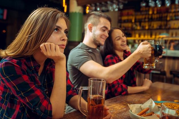Mensen, vrije tijd, vriendschap en communicatieconcept - gelukkige vrienden die bier drinken, spreken en glazen klinken bij bar of bar Gratis Foto