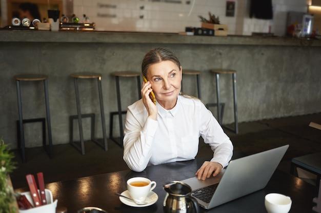 Mensen, werk, moderne levensstijl, technologie en communicatieconcept. foto van aantrekkelijke zelfverzekerde rijpe zakenvrouw in formele slijtage met telefoontje durign koffiepauze in café en met behulp van laptop Gratis Foto