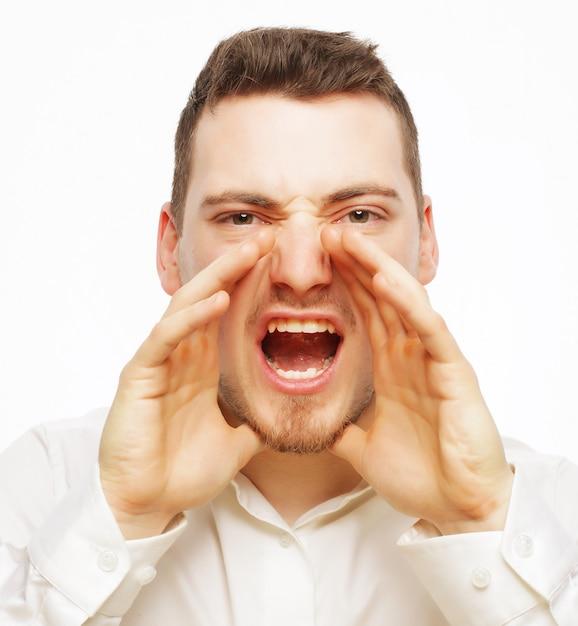 Mensen, zaken en lifestyle concept - knappe zakenman in wit overhemd schreeuwen tijdens het kijken naar camera en staande tegen witte ruimte Premium Foto