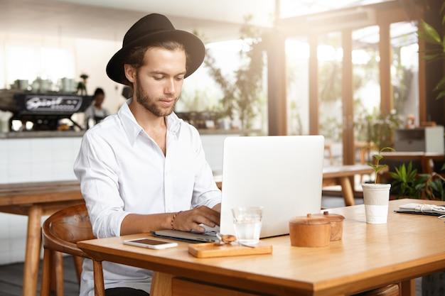 Mensen, zaken en moderne technologie. ernstige en gefocuste knappe man zit aan café tafel met glas water en mobiele telefoon tijdens het ontbijt, handen houden op toetsenbord van zijn generieke laptop Gratis Foto