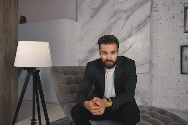 Mensen, zaken, stijl en luxe concept. foto van succesvolle jonge europese bebaarde man met dure polshorloge en elegant pak ontspannen in de moderne luxe woonkamer op de bank Gratis Foto