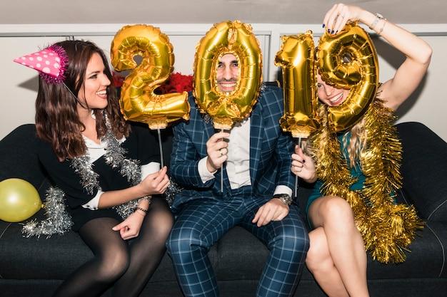 Mensen zitten met 2019 inscriptie van ballonnen Gratis Foto