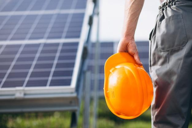 Mensenarbeider in firld door de zonnepanelen Gratis Foto