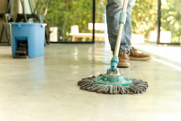 Mensenarbeider met zwabber en emmer schoonmakende vloer in het koffie. Premium Foto