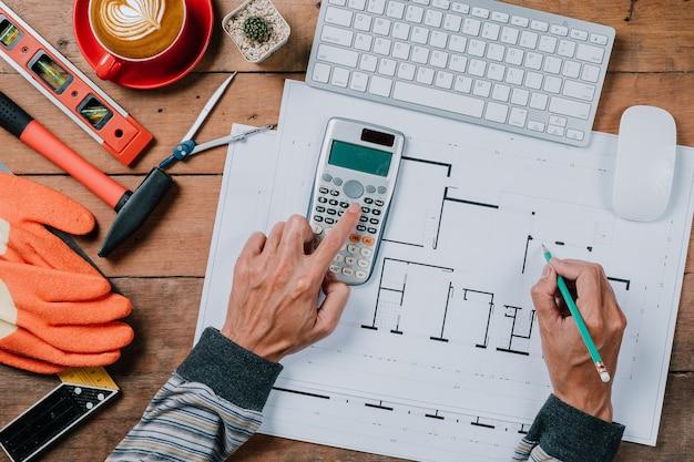Mensenconcept architectenhanden die met calculator en pen aan huis blauwe druk werken. Premium Foto