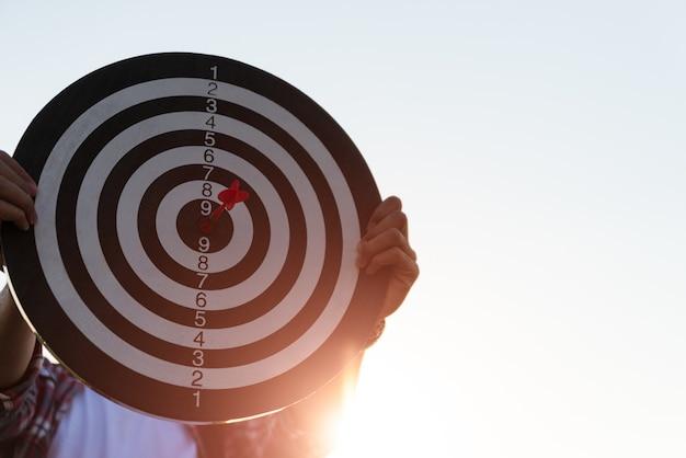 Mensenhand die een doel met pijltjes houden die het centrum raken. concept van zakelijke doelgroep. Premium Foto
