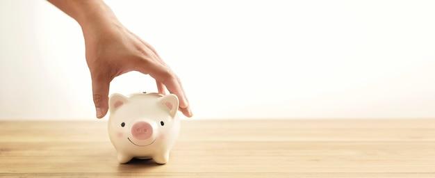 Mensenhand die spaarvarken op houten lijst houden. een besparingsgeld voor toekomstig investeringsconcept. Premium Foto