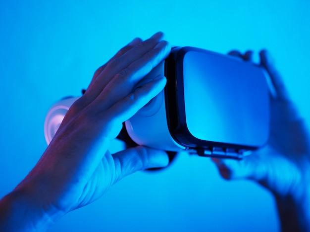 Mensenhanden die 3d 360 vr hoofdtelefoonglazen in futuristisch purper blauw neonlicht houden. Premium Foto