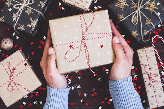 Mensenhanden die de vakantiedoos van de kerstmisvakantie op verfraaide feestelijke lijst houden Gratis Foto