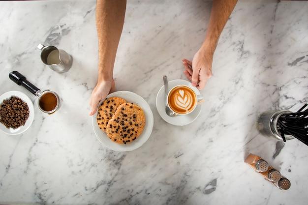 Mensenhanden met koekjes en een cappuccino Gratis Foto