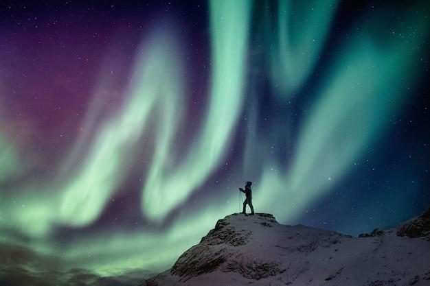 Mensenklimmer die zich op sneeuwpiek met dageraadborealis en sterrige achtergrond bevinden Premium Foto