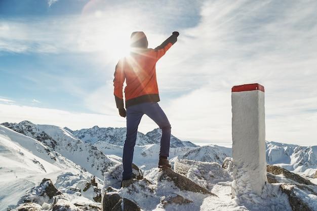 Mensenreiziger in de bergen met zijn opgeheven hand aangezien de winnaar zich bovenop bevindt Premium Foto