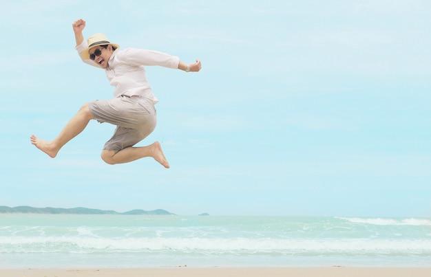 Mensensprong gelukkig tijdens vakantie op zee strand van thailand Gratis Foto