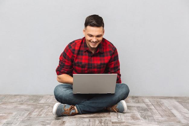 Mensenstudent die aan laptop werken terwijl het zitten op de vloer Gratis Foto