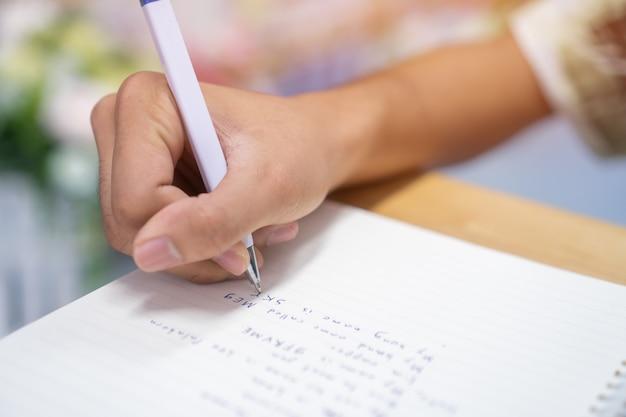 Mensenstudent die en nota's over notitieboekje met pen in bibliotheek nemen bij universiteitsuniversiteit voor thuiswerk nemen Premium Foto