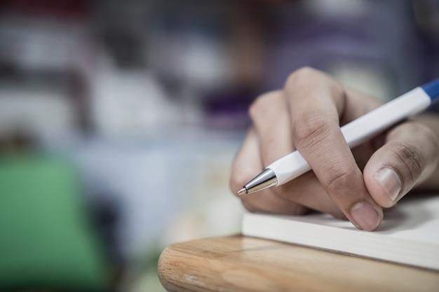 Mensenstudent die en nota's over notitieboekje op universiteitsuniversiteit voor thuiswerk nemen schrijven Premium Foto