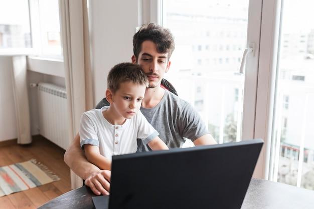 Mensenzitting met zijn zoon die laptop met behulp van Gratis Foto