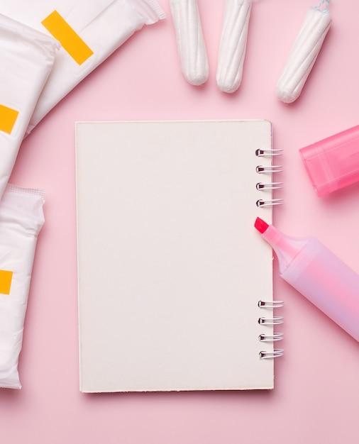 Menstruatie bij vrouwen. een leeg notitieboekje naast een stift, maandverband en tampons. Premium Foto