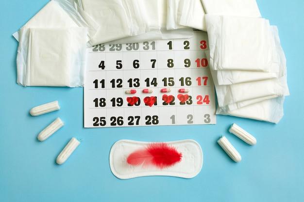 Menstruatiecyclus concept. menstruatiekalender met maandverband, anticonceptiepillen, tampons Premium Foto