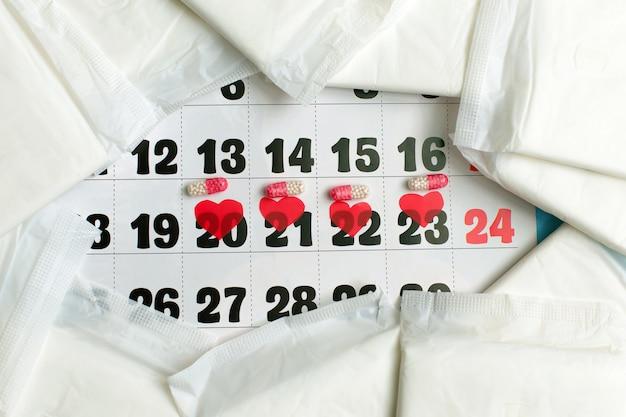 Menstruatiecyclus concept. menstruatiekalender met maandverband, anticonceptiepillen. Premium Foto